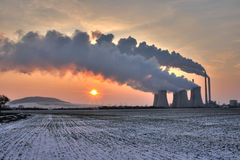 View of coal powerplant against sun and huge fumes. View of coal powerplant against sun with several chimneys and huge fumes stock photography