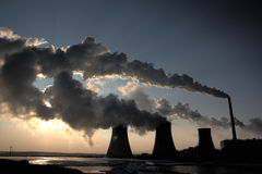 View of coal powerplant against sun and huge fumes. View of coal powerplant against sun with several chimneys and huge fumes royalty free stock images