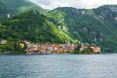 View on coast line of Lake Como, Italy, Lombardy region. Italian landscape, with Mountain and city with many colorful buildings on Stock Images