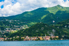 View on coast line of Lake Como, Italy, Lombardy region. Italian landscape, with Mountain and city with many colorful buildings on Royalty Free Stock Image