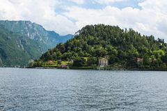 View on coast line of Lake Como, Italy, Lombardy region. Italian landscape, with Mountain and city with many colorful buildings on Stock Photos