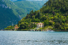 View on coast line of Lake Como, Italy, Lombardy region. Italian landscape, with Mountain and city with many colorful buildings on Stock Photo