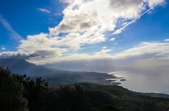 View of the coast and the mountains and a very blue sky with clouds and a vapor trail and the sun highlighting the edge of the oce. A view of the coast and the Stock Photo