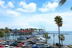 View of a coast with parked boats. And palm trees on blue sky background. Aruba royalty free stock photos