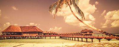 View of the coast of tropical island in Indian ocean with water bungalows. Maldives with vintage matte colored style stock image