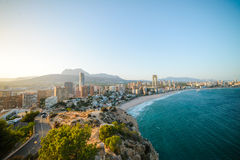 View of the coastline in Benidorm at sunset. Breathtaking view of the coastline in Benidorm at sunset with high buildings, mountains and sea Stock Image