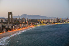 View of the coastline in Benidorm at sunset with city lights. Breathtaking view of the coastline in Benidorm at sunset with high buildings, mountains, sea and Stock Photography