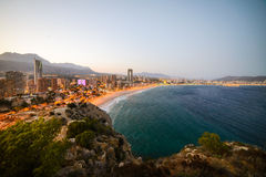View of the coastline in Benidorm at sunset with city lights. Breathtaking view of the coastline in Benidorm at sunset with high buildings, mountains, sea and Stock Photo