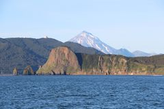 View of coastline of the Kamchatka Peninsula, Russia. In the background is visible Vilyuchinsky volcano also called Vilyuchik. It`s a stratovolcano in the royalty free stock images