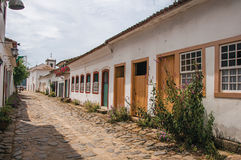 View of cobblestone alley with old colorful houses and blue cloudy sky in Paraty. Stock Images