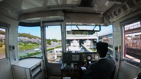 Japan train. View from the cockpit with beautiful cherry blossom along the Expo `70 Commemorative Park. Train driver driving to Osaka Monorail station stock footage