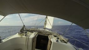 View from the cockpit towards the bow of a sailing marine yacht sailing on the waves in the open sea on a sunny summer day. Walk a stock video