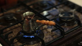 A view of coffee in a coffee pot with a long handle preparing on fire. stock video