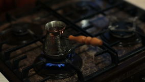 A view of coffee in a coffee pot preparing on fire. A view of coffee in a coffee pot with a long handle preparing on fire stock footage