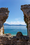 Old ruined historic stone wall overlooking the sea. View through the collapsed window in an old ruined historic stone wall overlooking the sea and coastline on a Stock Photos