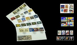Colourful postage stamps and first day covers. View of a collection of stamps and first day covers on a black background stock image