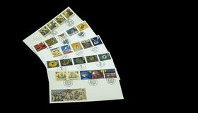 Colourful postage stamps and first day covers. View of a collection of stamps and first day covers on a black background royalty free stock photos