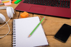 View on college student desk top workspace. With note pad with lap top pencil and headphones on desk Stock Images