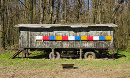 A view of the colorful apiary with wheels bees standing in a meadow surrounded by forest trees Stock Image