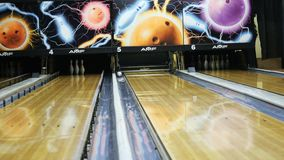 View of colorful ball hitting the bowling pins on bowling alley in a sport club. Media.The bowling balls return machine. View of colorful ball hitting the stock video footage