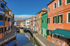 View of colorful buildings, people and boats in front of a canal at Burano. royalty free stock images