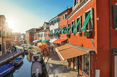 View of colorful buildings, people and boats in front of a canal at Burano. royalty free stock photos