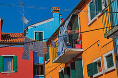 View of colorful terraced houses, balcony and clothes hanging in an alley in Burano. Royalty Free Stock Images