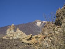 View on colorful volcano pico del teide highest spanish mountain. From famous pitoresque rock formation Roques de Garcia with clear blue sky and dry trees Stock Images