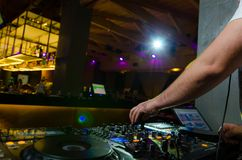 View of the colourful controls on the deck with the hands of a DJ mixing music at a concert stock image