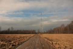 View on the communications tower and road to the forest. Against a blue sky with white clouds Stock Photos