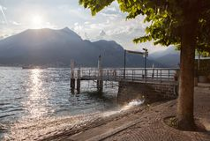 View of Como lake on sunset with pier in Italy Royalty Free Stock Image