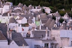 View of the conical dry stone roofs of the traditional trullo dry stone houses in Alberobello in Puglia Italy. Photographed at sunrise from a vantage point stock photo