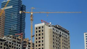 View on a construction crane and unfinished building in modern city in summer day. Against clear blue sky stock footage