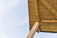 View of the construction of a pitched roof and clear blue sky. With copy space royalty free stock image