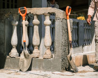 View of construction site with shovels standing against fresh build classic retro style concrete fence. Fragment of view of construction site with shovels Royalty Free Stock Image