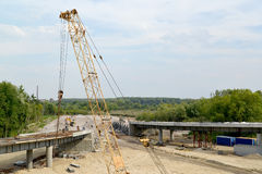 View of construction of a traffic intersection with a crane arrow in the foreground.  Royalty Free Stock Images