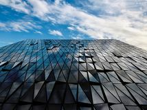 Skyscraper reflecting clouds in the sky royalty free stock image