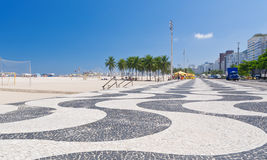 View of Copacabana beach with palms and mosaic of sidewalk in Rio de Janeiro Stock Image
