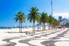 View Copacabana beach with palms and mosaic of sidewalk in Rio de Janeiro Stock Photo