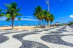 View of Copacabana beach with palms and mosaic of sidewalk in Rio de Janeiro. Brazil stock photography