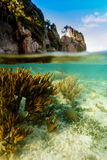 View of coral reef underneath and cliff caves above waterline in Caribbean. Sea royalty free stock image