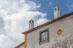 View of cornice and upper corner of building facade, traditional chimney. On the medieval village of Obidos, Portugal windows frame detail architecture royalty free stock images