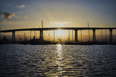 View from Coronado Island through the Coronado Bridge into the industrial oceanfront area. A cool night gives way to a warm and inviting sunrise in San Diego stock photo