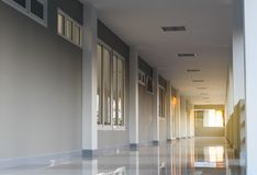 View of the corridor inside the gray building. View inside the entrance to the corridor in front of the shade of a gray building with early morning orange shine Royalty Free Stock Image