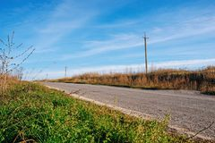 View on the countryside asphalt road laid between green grass and blue sky.  Royalty Free Stock Images