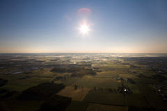 View of a countryside with sun. View of a countryside with sun in center - shot from a hot air balloon Stock Photo