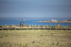 View of couple walking on pedestrian wooden walkway, near the sea stock photo