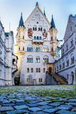 View of Neuschwanstein Castle in Fussen, Bavaria, Germany. View of courtyard of Neuschwanstein Castle with cobbled paved courtyard illuminated by evening sunset royalty free stock photos