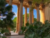 View from the courtyard of the University on the colonnade. In sunny evening with a lot of different plants stock image