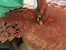 View of craftsman carves leather. Close up view of craftsman carves a pattern on leather Stock Photos